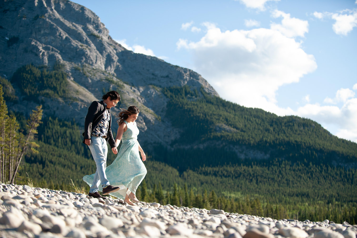Couple stroll on the rocky shore of Barrier Lake captured by Tara Whittaker Photography