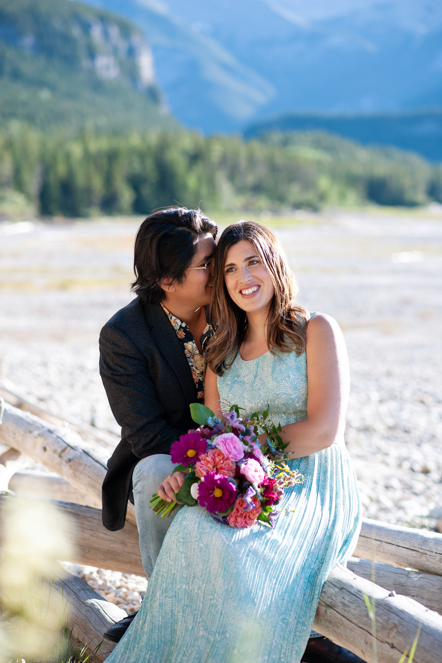 Couple snuggle on a log next to Barrier Lake captured by Tara Whittaker Photography