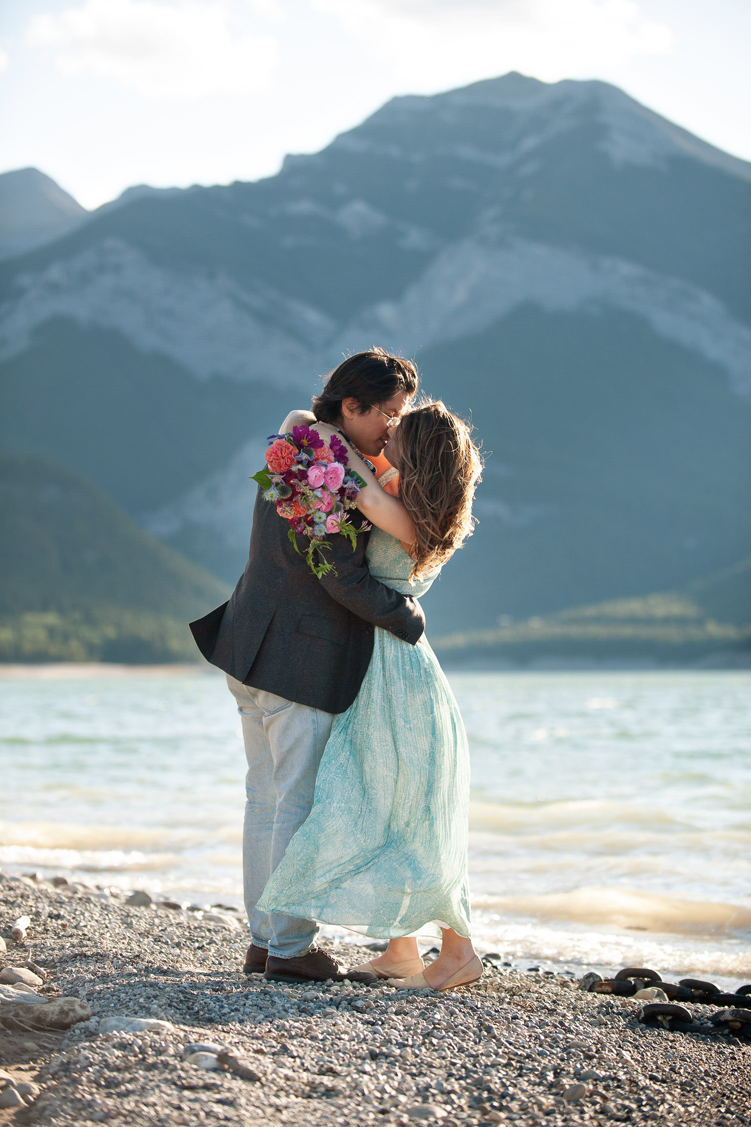 Couple kiss on the shore of Barrier Lake captured by Tara Whittaker Photography