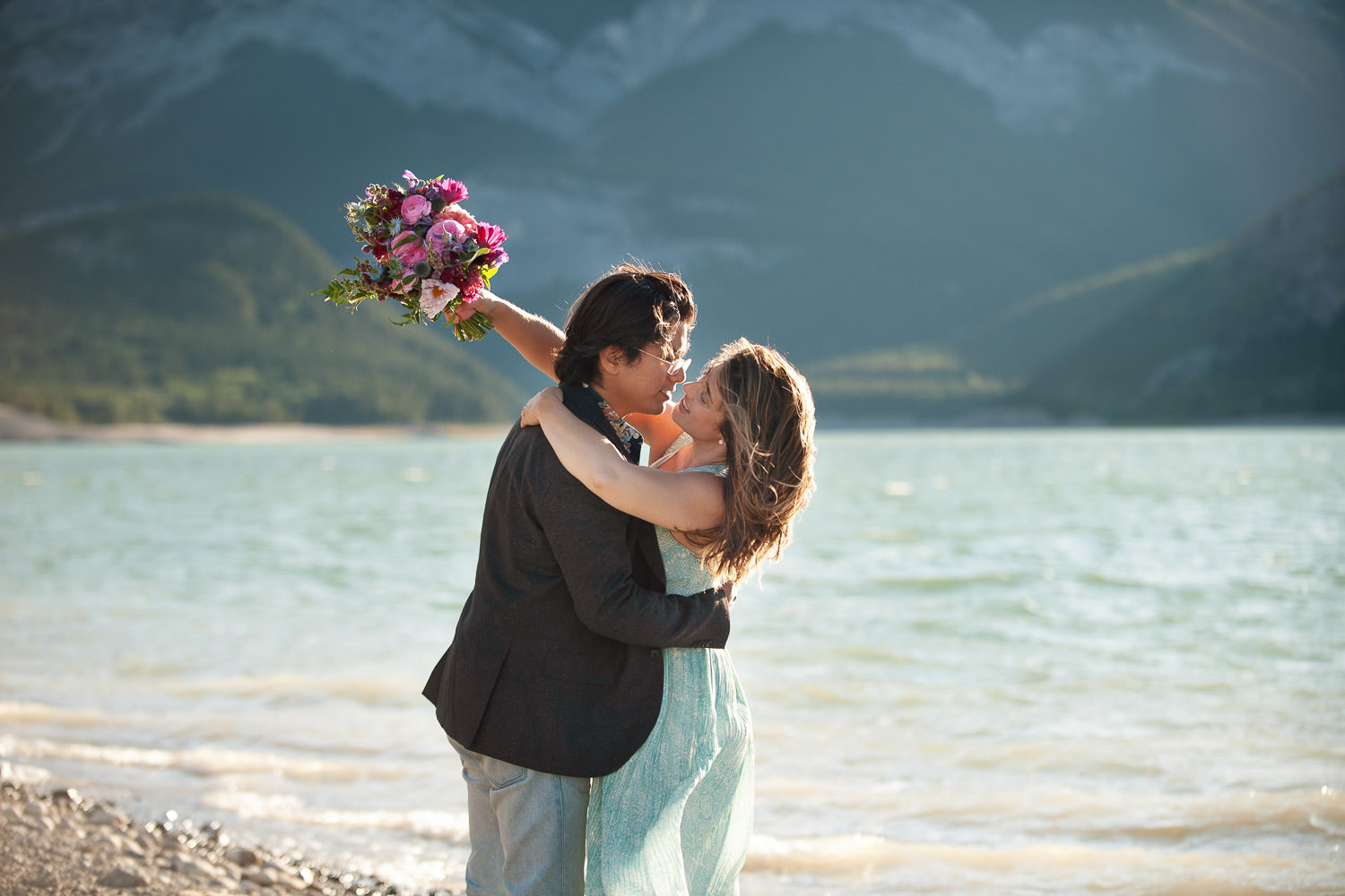 Couple embrance on the shore of Barrier Lake captured by Tara Whittaker Photography